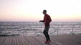 Ansicht in voller Länge des starken und motivierten Sportlers, der nahe dem Meer aufwärmt Trainieren, Ausbildungsfreien seite stock footage