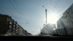 Ansicht vom Auto zur Stadt Fokus auf der schmutzigen Windschutzscheibe stock footage