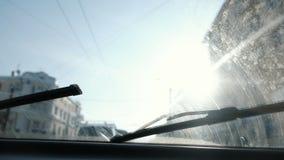 Ansicht vom Auto zur Stadt Fokus auf der schmutzigen Windschutzscheibe Die Scheibenwischer funktionieren stock video