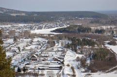 Ansicht vom Berg auf einem entfernten sibirischen Dorf Die Winterlandschaft Lizenzfreie Stockfotos