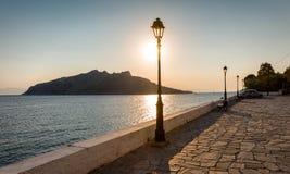 Ansicht vom Dorf von Perdika, Aegina-Insel zu Moni Island während des Sonnenuntergangs Stockfotos