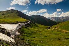 Ansicht vom Durchlauf zum grünen Tal und zu den Bergen Stockbild