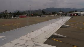 Ansicht vom Fenster auf dem Flügel eines Flugzeuges, das entlang die Rollbahn am Flughafen nach der Landung sich bewegt stock footage