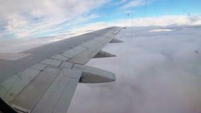Ansicht vom Fenster auf dem Flügel eines Passagierflugzeugfliegens niedrig über den Wolken stock video footage