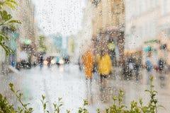 Ansicht vom Fenster auf Stadtstraße Regnerischer Tag in der Stadt Leute, zwei Mädchen gesehen durch Regentropfen auf Glas vorgewä Lizenzfreies Stockfoto