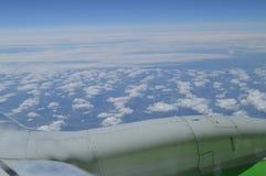 Ansicht vom Fenster der Flugzeuge auf der Turbine und dem Flügel gegen den blauen Himmel und die Wolken Stockfotos