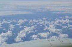 Ansicht vom Fenster der Flugzeuge auf der Turbine und dem Flügel gegen den blauen Himmel und die Wolken Lizenzfreie Stockfotografie