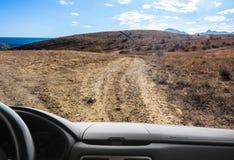 Ansicht vom Fenster des Autos auf dem Schotterweg des Berges stockbild