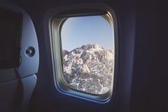 Ansicht vom Fensterflugzeug Außerhalb kann Schnee, Baum und Sonnenuntergang sehen lizenzfreie stockbilder
