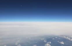 Ansicht vom Flugzeugfenster, vom blauen Himmel und von den weißen Wolken Stockfotos