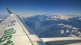 Ansicht vom Flugzeugfenster von Bergen mit Schnee auf der Spitze, den Wolken, dem Flügel und dem blauen Himmel Lizenzfreie Stockfotos