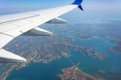 Ansicht vom Flugzeugfenster Wolken und Landschaft unter dem Flügel Lizenzfreie Stockfotos