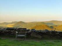 Ansicht vom Hügel über Restplatz mit altem Holzstuhl unten zur Landschaft Frühlingsmorgen? Feld des grünen Grases und des blauen  Lizenzfreies Stockbild