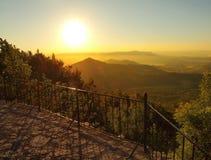 Ansicht vom Hügel über Restplatz mit altem Holzstuhl unten zur Landschaft Frühlingsmorgen? Feld des grünen Grases und des blauen  Stockfoto