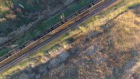 Ansicht vom Himmel auf einem Güterzug geladen mit Kohle, unbemannter Flug über dem Güterzug, der den Fluss kreuzt stock video footage