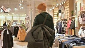 Ansicht vom hinteren Mädcheneinkaufen in einer Strickjacke und in den Hutwegen durch ein Bekleidungsgeschäft Livekamera stock footage