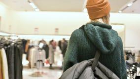 Ansicht vom hinteren Mädcheneinkaufen in einer Strickjacke und in den Hutwegen durch ein Bekleidungsgeschäft Livekamera stock video
