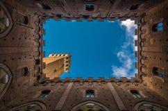 Ansicht vom Hof des mittelalterlichen Siena-Rathauses, Palazzo Pubblico, zu Mangia-Turm, zu Torre Del Mangia und zum blauen Himme lizenzfreies stockfoto