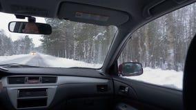 Ansicht vom Rücksitzauto, das Winterstraße weitergeht Frauenfahrer, der in schneebedeckte Straße fährt stock video footage