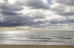 Ansicht vom Sandstrand von schwerem mediteranean Meer mit Wellen und Cl Lizenzfreies Stockfoto