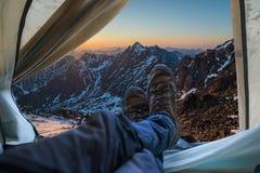 Ansicht vom Zelt auf Schnee-mit einer Kappe bedeckten Bergen Reisen und Expeditionen im wilden Konzept des Kampierens lizenzfreies stockfoto