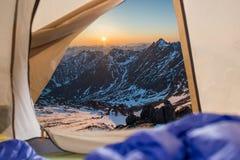 Ansicht vom Zelt auf Schnee-mit einer Kappe bedeckten Bergen Reisen und Expeditionen im wilden Konzept des Kampierens stockfoto