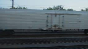 Ansicht vom Zugfenster, ein weißer Waggon steht auf der Eisenbahn stock video footage