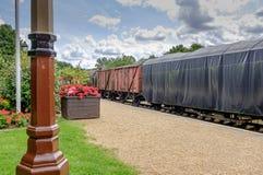 Ansicht von altmodischen bedeckten Frachtpackwagen und von Lastwagen gesehenem Ausschiffen von einer Bahnplattform lizenzfreie stockfotografie