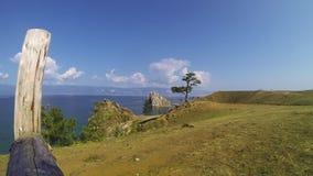 Ansicht von Baikal vom Ufer Auf dem Ufer sind Steine, Büsche, ein Baum Baum mit farbigen Farbb?ndern Olkhon Insel stock video footage