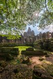 Ansicht von Bayon-Tempel mit Felsen und von Baumastvordergrund bei Siem Reap, Kambodscha lizenzfreies stockbild