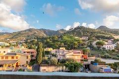 Ansicht von Bergen, Landhäuser, Bäume unter blauem bewölktem Himmel Stockbild