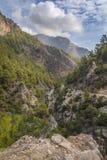 Ansicht von Bergen, von Bäumen, von Fluss, von Himmel und von steiniger Straße Lizenzfreie Stockfotos