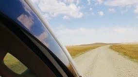Ansicht von beweglichem Auto des Fensters auf staubiger Landstraße mit Wüstenfeldern und -hügeln stock video