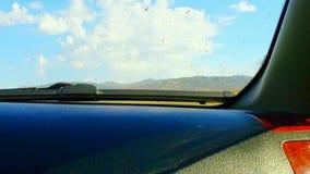Ansicht von beweglichem Auto des Fensters auf staubiger Landstraße mit Wüstenfeldern und -hügeln stock footage