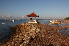 Ansicht von blauem Meer, von Booten und von Steinpier mit Pavillon in Bali Stockfoto