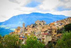 Ansicht von Caccamo-Stadt auf dem Hügel mit Gebirgshintergrund am bewölkten Tag in Sizilien Stockfotos