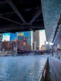 Ansicht von Chicago Riverwalk mit dem Dampf, der über ihm durchbrennt und der Chicago River als Temps tauchen stockfotografie
