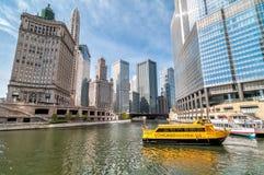 Ansicht von Chicago-Wolkenkratzern mit dem Besichtigungsboot Watertaxi und Wendell, das auf dem Chicago River kreuzt Stockfotografie