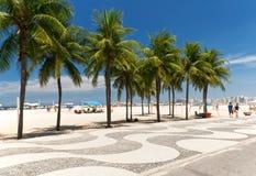 Ansicht von Copacabana-Strand mit Palmen und von Mosaik des Bürgersteigs in Rio de Janeiro Stockfotografie