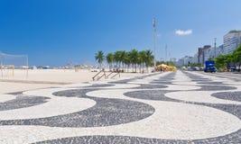Ansicht von Copacabana-Strand mit Palmen und von Mosaik des Bürgersteigs in Rio de Janeiro Stockbild