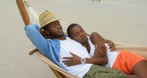Ansicht von den Afroamerikanerpaaren, die in einer Hängematte auf dem Strand 4k schlafen stock video footage