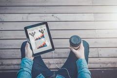 Ansicht von den Augen Nahaufnahme der digitalen Tablette mit leerem Bildschirm und Tasse Kaffee in den Händen des Hippie-Mannes Stockbild