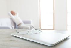 Ansicht von den Gläsern, die auf dem modernen Laptop mit dem stillstehenden Mann sitzt auf skandinavischem Designsofa liegen Lizenzfreie Stockfotografie