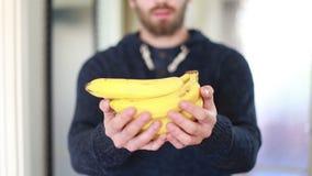 Ansicht von den Mannhänden, die Bananen halten stock footage