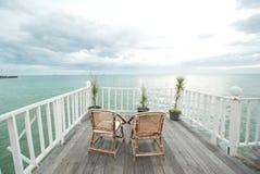 Ansicht von den weißen Terrassen mit Holzstühlen stockfoto