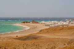 Ansicht von den wilden Wellen, die über Coral Reef und Beduine-Zelten im Wind auf Strand in Marsa Alam zusammenstoßen lizenzfreie stockfotografie