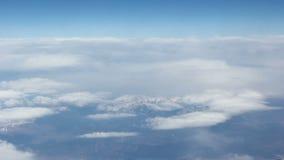 Ansicht von den Wolken zu den Schnee-mit einer Kappe bedeckten Bergen Schießen von der sehr großen Höhe Schöner blauer Himmel stock footage