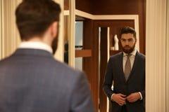 Ansicht von der Rückseite des Mannes den Spiegel betrachtend Stockfotografie