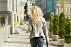 Ansicht von der Rückseite der jungen Blondine, die entlang Stadtstraße, sonniger Tag des Herbstes, goldene Stunde gehen stockfoto