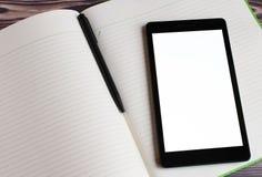 Ansicht von der Seite eines schwarzen Laptops, der auf dem geöffneten großen Notizbuch liegt In der Mitte des Notizbuches ist ein stockbilder